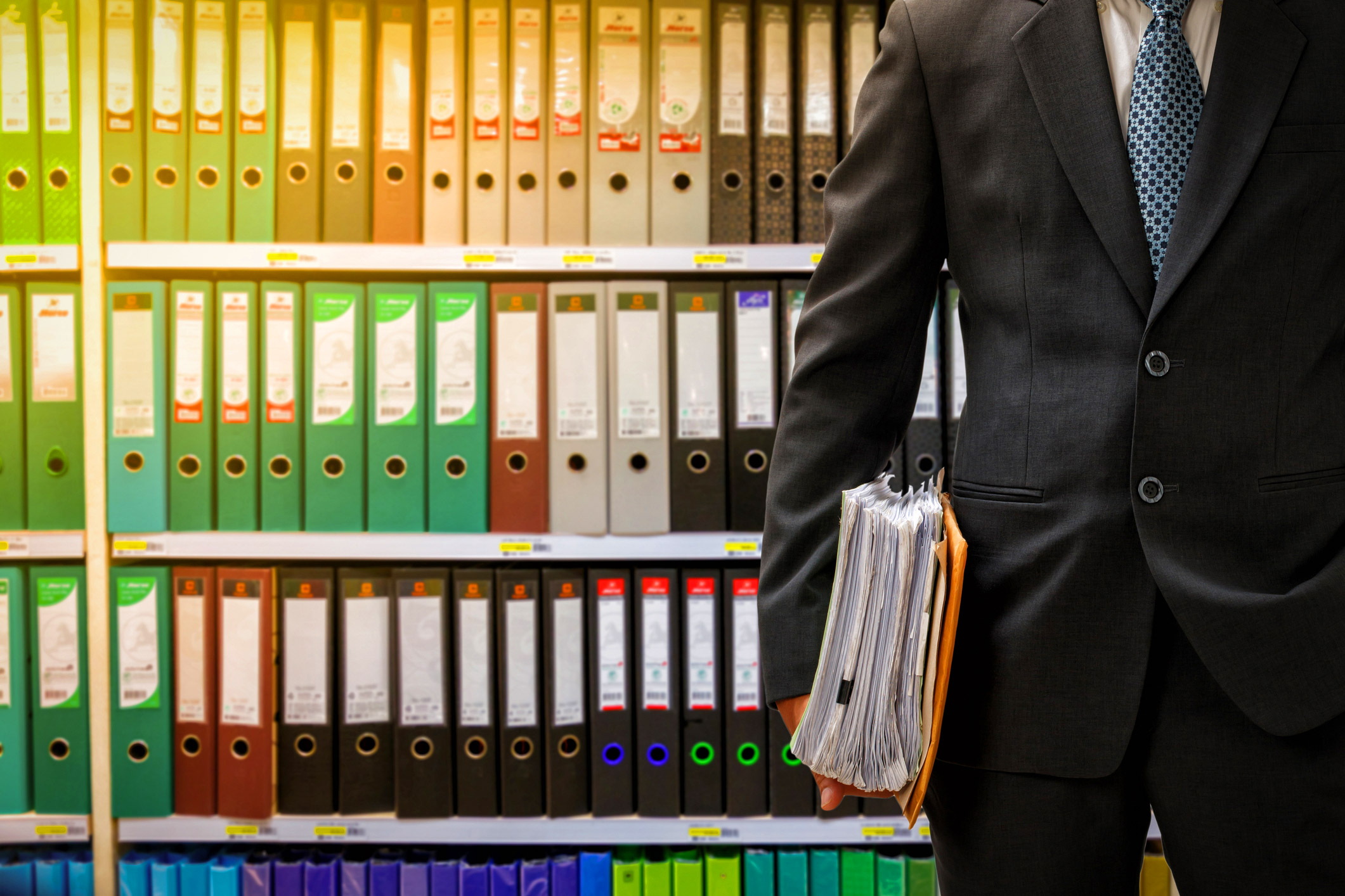 Businessman-holding-data-files-in-front-of-color-files