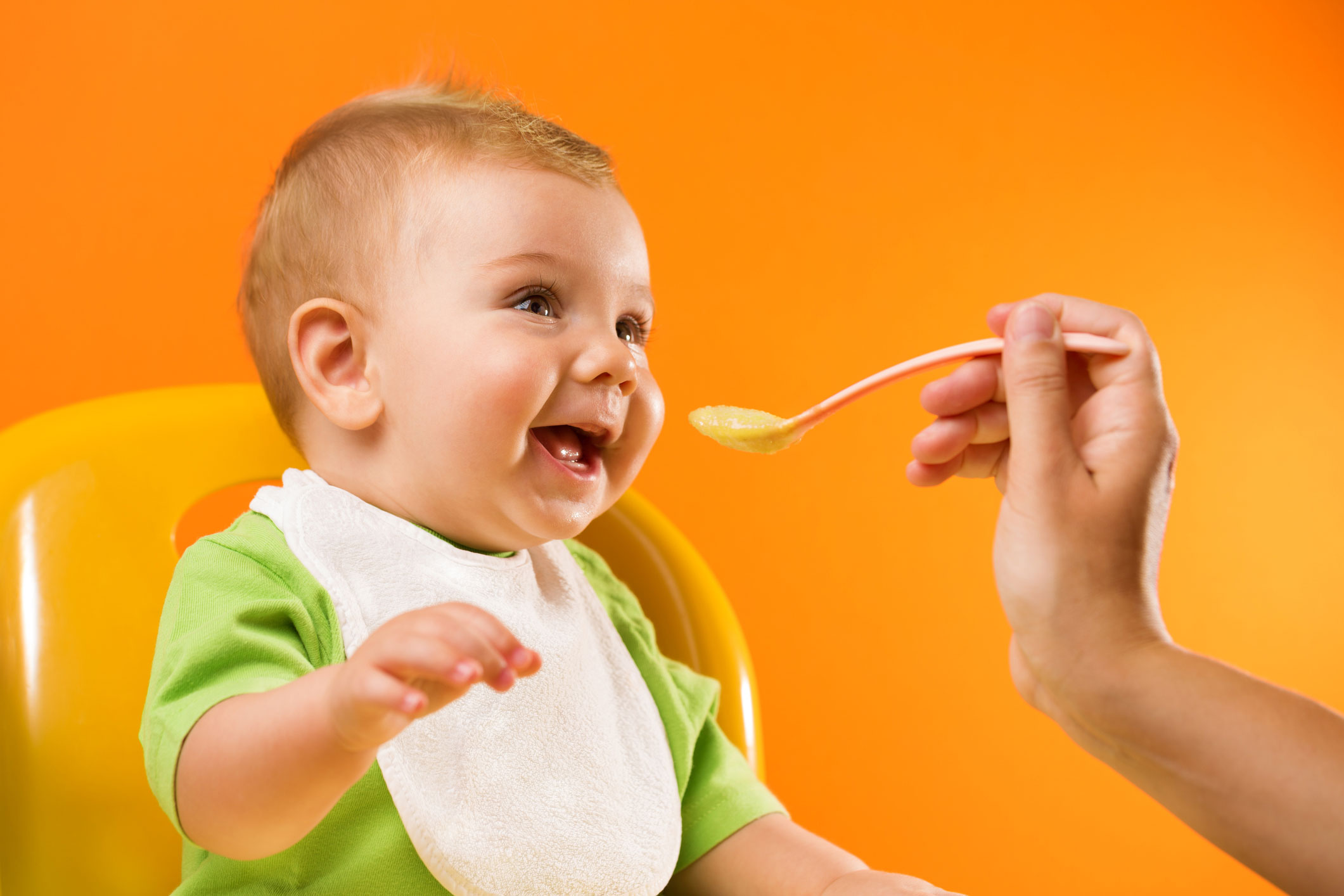 Feeding-cheerful-baby-on-orange-background