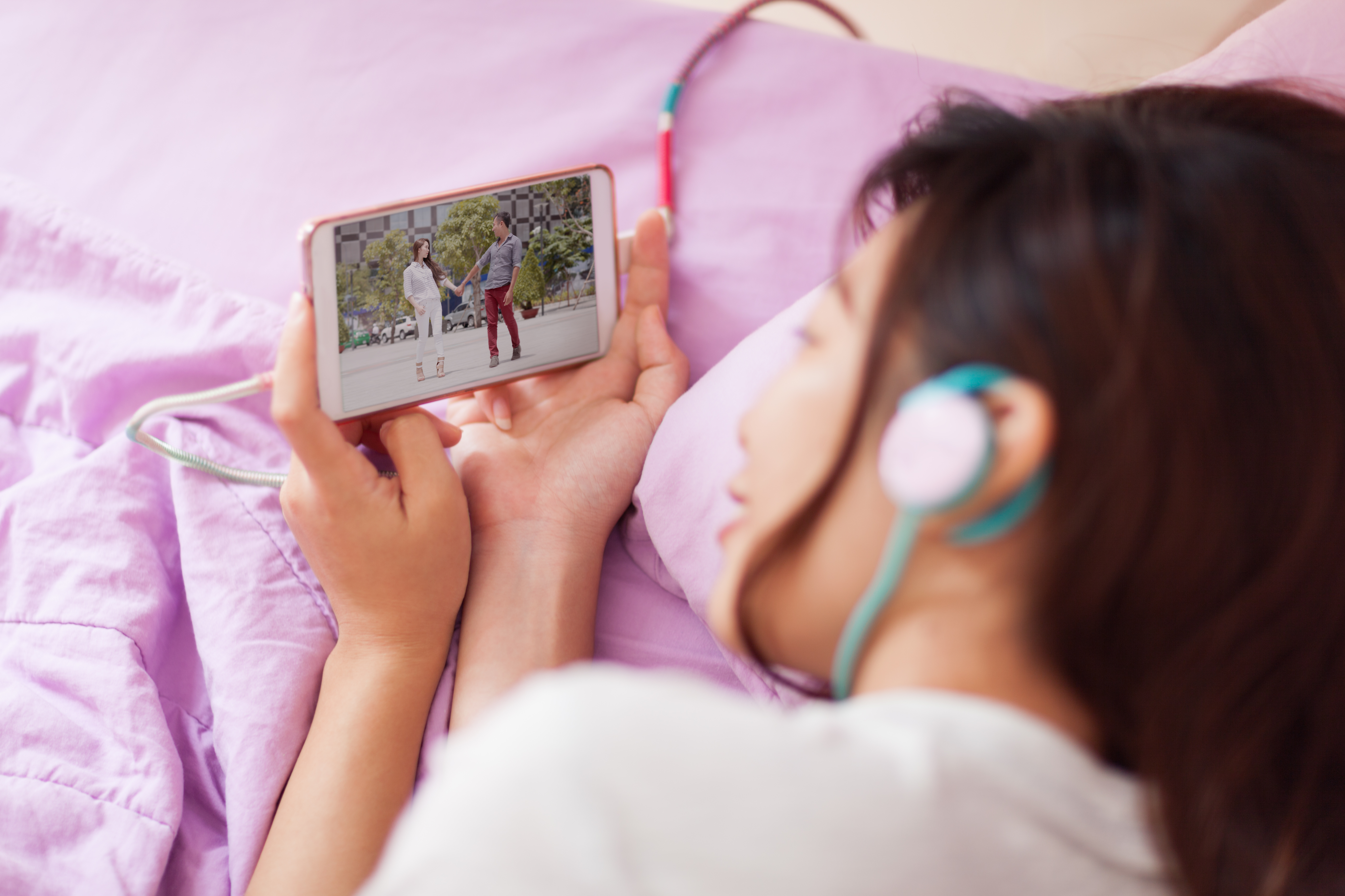 Girl_Watching_Mobile_Video_Smart_Phone_with_Headphones
