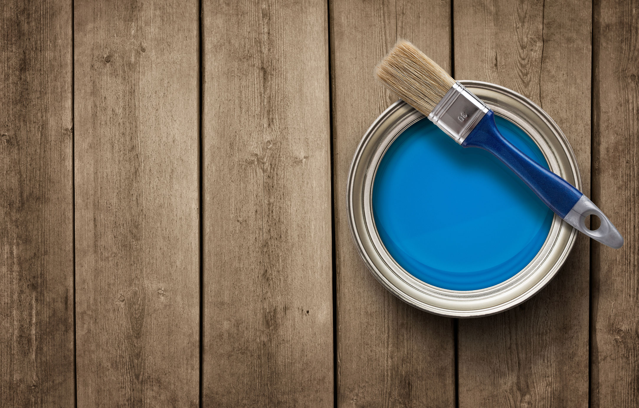 Paint-can-and-brush-on-wood-background