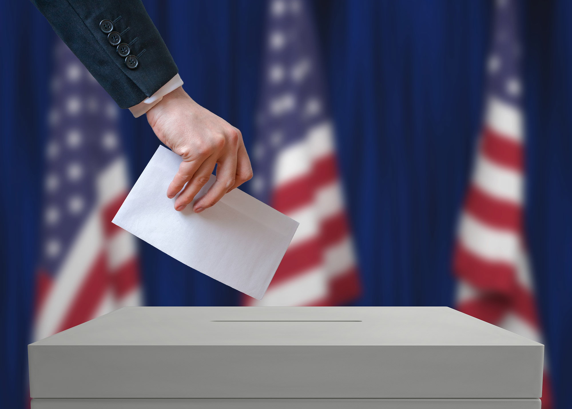 Voter-holds-envelope-in-hand-above-vote-ballot