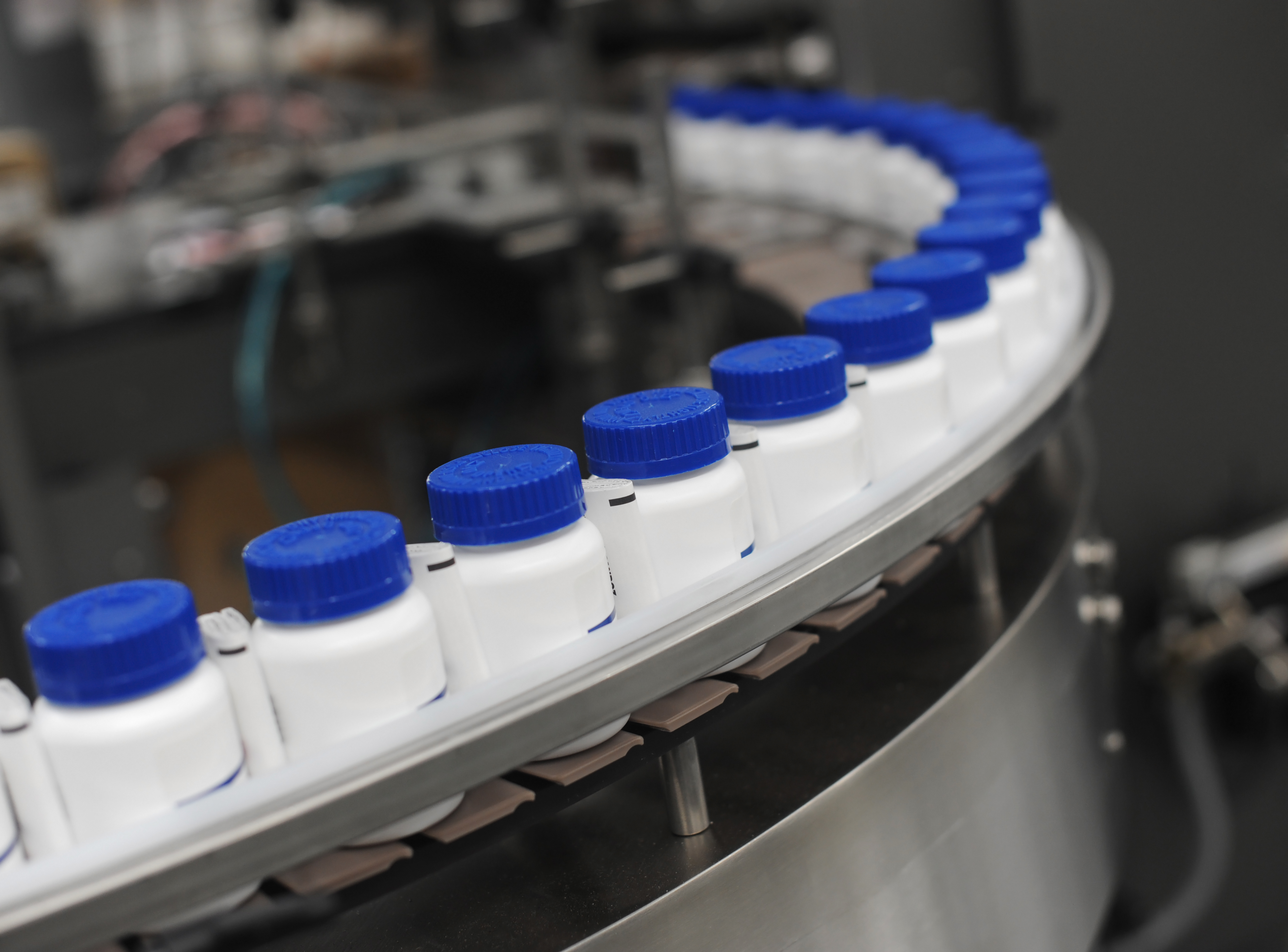 Blue-Capped-Drug-Bottles-on-Conveyor
