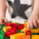 Close-up-of-childs-hands-playing-with-colorful-plastic-bricks-at-the-table
