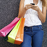 Woman-Texting-with-Shopping-Bags
